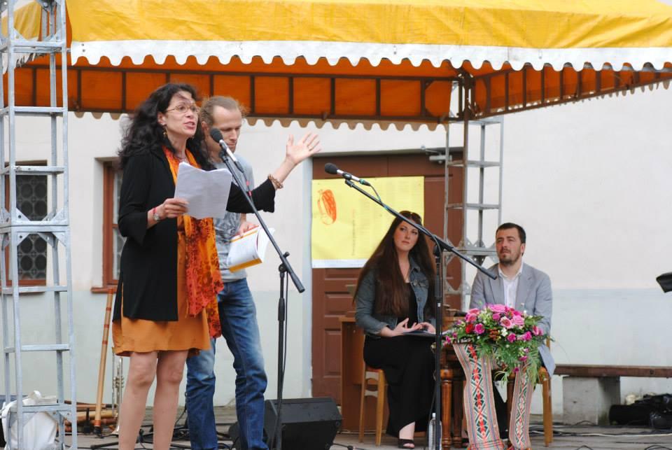 Heather Thomas declaiming a poem; with her, Lithuanian poet, Marius Burokas